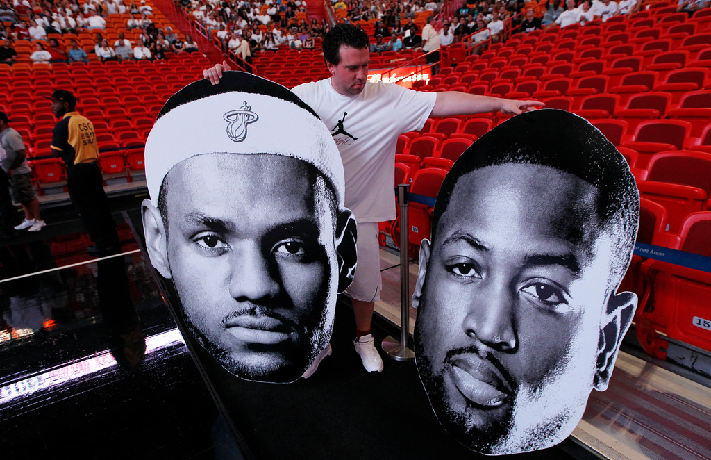 . Billy O\'Rourke, of the Miami Heat Xtreme Team, arranges cardboard cutouts of Miami Heat\'s LeBron James, left, and Dwyane Wade as fans watch a broadcast of the Boston-hosted Game 6 of the NBA basketball Eastern Conference finals between the Heat and Boston Celtics, Thursday, June 7, 2012, at American Airlines Arena in Miami. (AP Photo/Lynne Sladky)