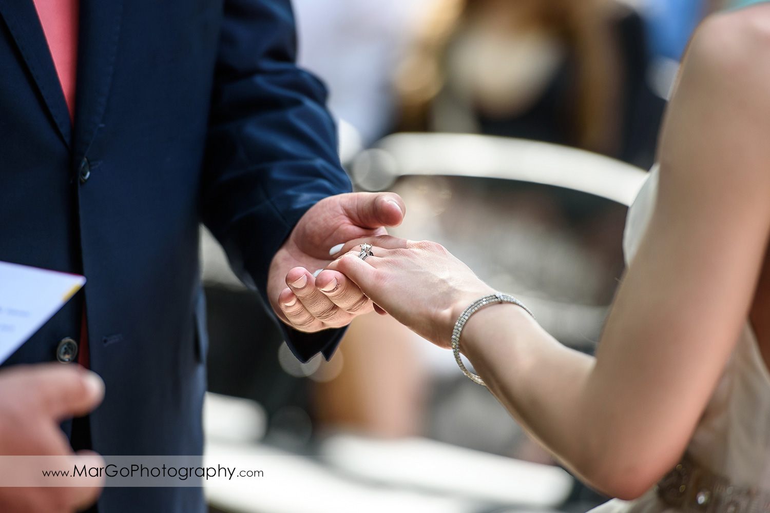 close-up of groom holding bride's hand during wedding ceremony at Saratoga Foothill Club