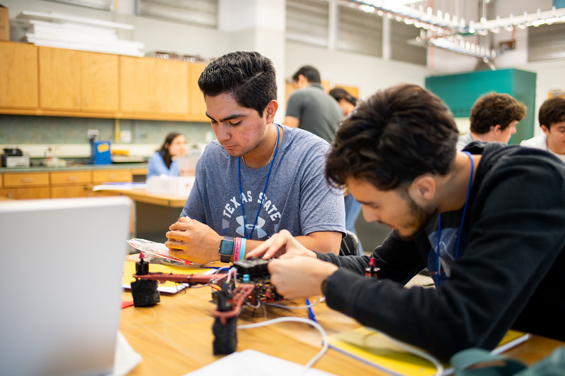 UAS Summer Program students attach modular components to their drones.