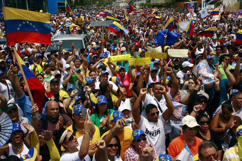 . Supporters of opposition leader Henrique Capriles take part in a demonstration to demand a recount of the votes in Sunday\'s election, in front of the office of the National Electoral Council (CNE), in Maracaibo April 16, 2013. Venezuelan President-elect Nicolas Maduro accused the opposition on Tuesday of planning a coup against him after seven government supporters were killed in violent clashes over his disputed election victory. Capriles has demanded a full recount of votes from Sunday\'s election after official results showed a narrow victory for Maduro, who is late socialist President Hugo Chavez\'s hand-picked successor. REUTERS/Isaac Urrutia