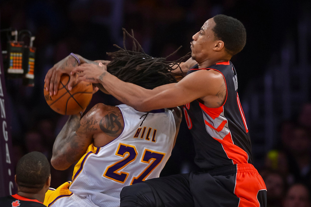 . Raptors� DeMar DeRozan fouls Lakers� Jordan Hill during second half action at Staples Center Sunday, December 8, 2013.  Lakers lost to the Raptors 94-106 as Bryant returned to action for the first time this season.  ( Photo by David Crane/Los Angeles Daily News )