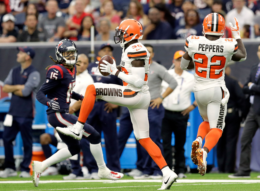 . Houston Texans\' Will Fuller V (15) watches Cleveland Browns cornerback Jason McCourty (30) intercept a pass in front of safety Jabrill Peppers (22) that McCourty returned for a touchdown in the second half of an NFL football game, Sunday, Oct. 15, 2017, in Houston. (AP Photo/Eric Gay)