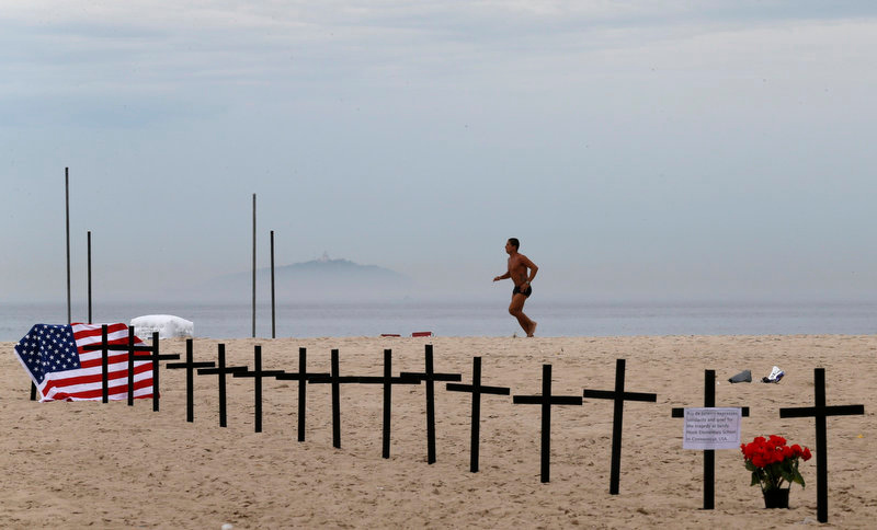 Description of . A resident runs near crosses planted by members of NGO Rio de Paz (Rio Peace), in memory of the victims of the Sandy Hook Elementary school shooting in the U.S., on Copacabana beach in Rio de Janeiro December 15, 2012. A heavily armed gunman opened fire on school children and staff at Sandy Hook Elementary school on Friday, killing at least 26 people, including 20 children, in the latest in a series of shooting rampages that have tormented the United States this year. REUTERS/Sergio Moraes
