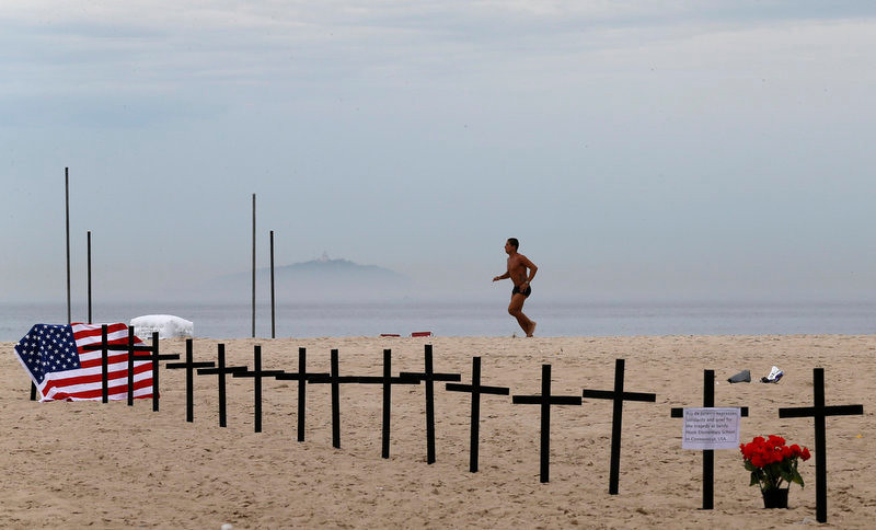 . A resident runs near crosses planted by members of NGO Rio de Paz (Rio Peace), in memory of the victims of the Sandy Hook Elementary school shooting in the U.S., on Copacabana beach in Rio de Janeiro December 15, 2012. A heavily armed gunman opened fire on school children and staff at Sandy Hook Elementary school on Friday, killing at least 26 people, including 20 children, in the latest in a series of shooting rampages that have tormented the United States this year. REUTERS/Sergio Moraes