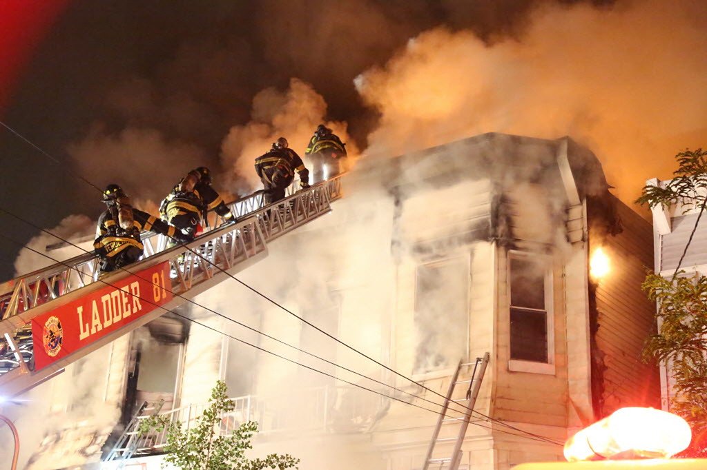 . Firefighters battle a fire that tore through three townhouses on New York City\'s Staten Island early Thursday, June 5, 2014. At least 34 people were injured, including two young children who were tossed out of a smoke-filled second-floor window into the arms of neighbors below, authorities and witnesses said. (AP Photo/Staten Island Advance, Ryan Lavis)