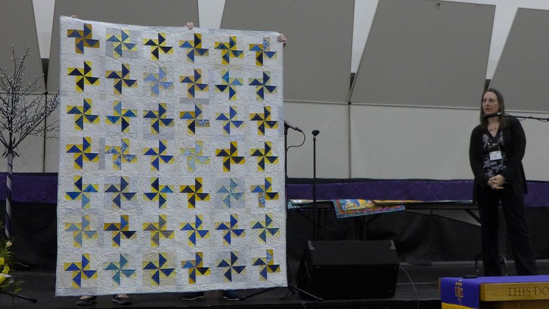 Kelly Sattler showing us a quilt that she quilted for a raffle sponsored by national librarian organization.