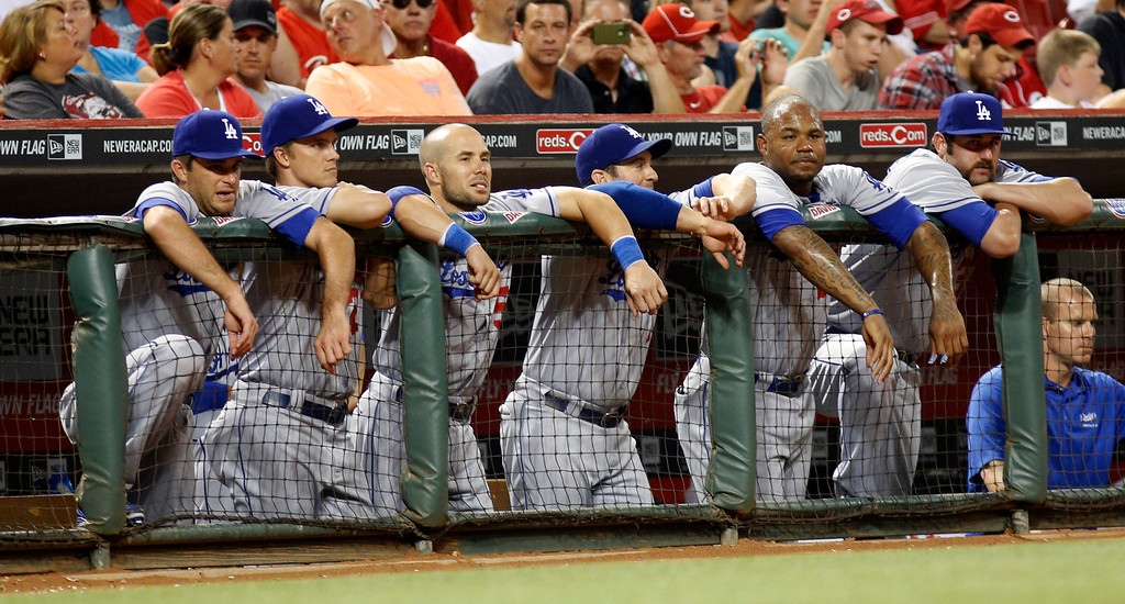 . Los Angeles Dodgers players lean on the dugout rail as they watch a baseball game against the Cincinnati Reds, Sunday, Sept. 8, 2013, in Cincinnati. (AP Photo/David Kohl)