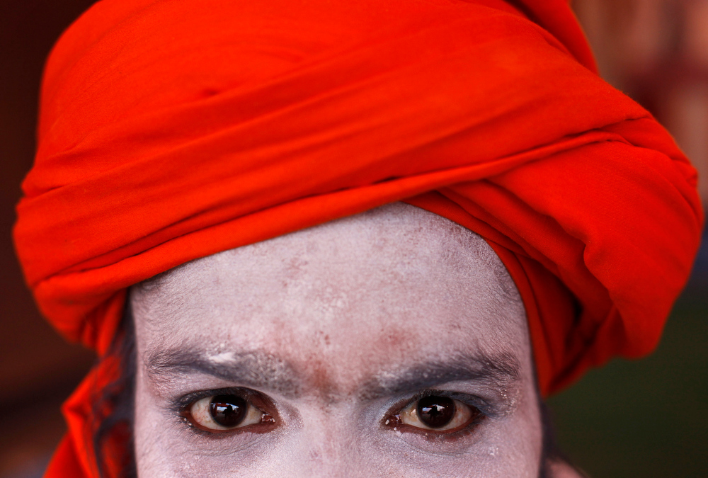 Description of . A Hindu holy man poses for a photograph at Sangam, the confluence of the Ganges and Yamuna rivers on the occasion of
