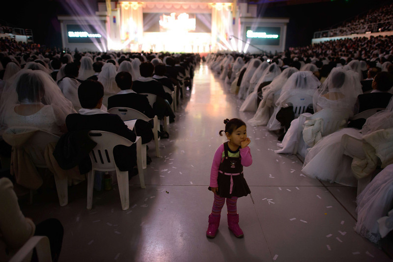 ". A child sucks her thumb as couples watch a performance during a mass wedding event held by the Unification Church in Gapyeong on February 12, 2014. Unification Church members forming 2500 couples from 52 countries were married in a mass wedding in South Korea -- only the second such event since the death of their ""messiah\"" and controversial church founder Sun Myung Moon. (ED JONES/AFP/Getty Images)"