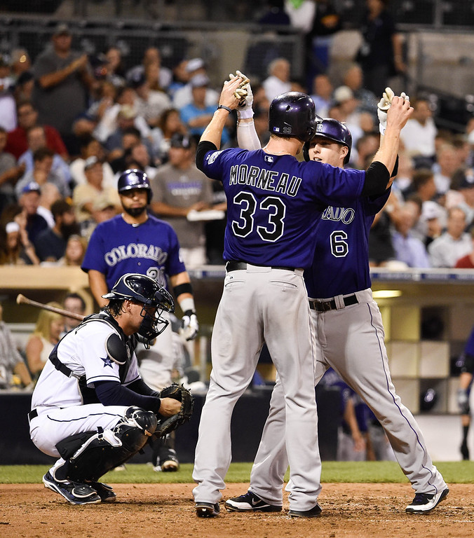 . Corey Dickerson #6 of the Colorado Rockies, right, is congratulated by Justin Morneau #33 after he hit a three run home run during the sixth inning of a baseball game against the San Diego Padres at Petco Park August, 11, 2014 in San Diego, California.  (Photo by Denis Poroy/Getty Images)