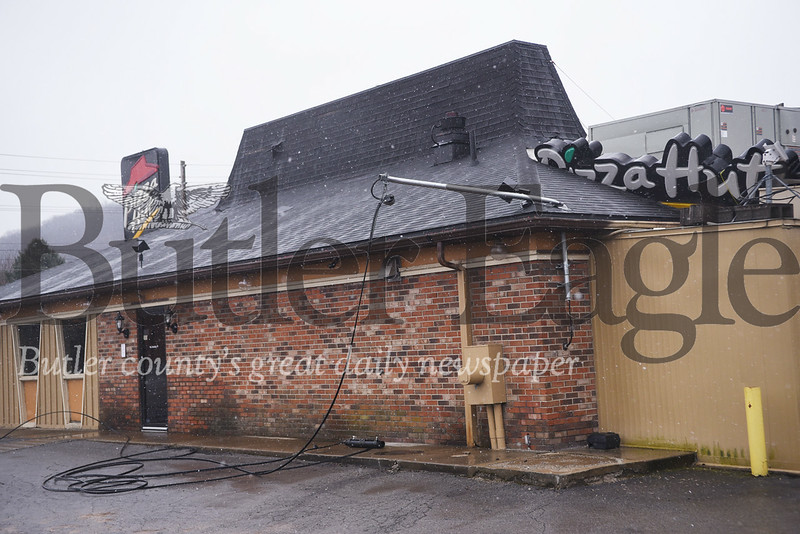 A utility line attached to the Pizza Hut on Route 8 in Butler Township is shown laying on the ground. The restaurant was closed Friday after an overnight electrical fire. Tanner Cole/Butler Eagle