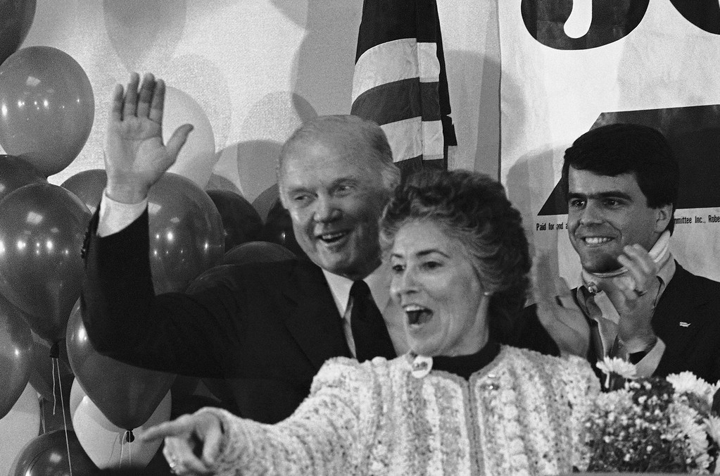 . Democratic presidential candidate Sen. John Glenn gives the thumbs up sign as his wife, Annie, gestures to a familiar face in the crowd of supporters that gathered at night on Tuesday, March 13, 1984 in Birmingham, Ala. (AP Photo/Dave Martin)