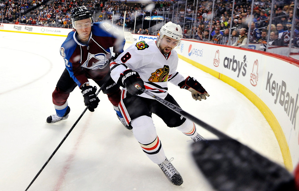 . Colorado Avalanche right wing Chuck Kobasew (12) and Chicago Blackhawks defenseman Nick Leddy (8) chase a puck into the corner during the third period of an NHL hockey game, Monday, March 18, 2013, in Denver. Chicago won 5-2. (AP Photo/Jack Dempsey)