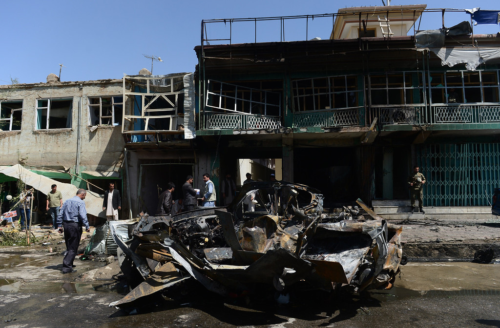 . Afghan men walk around a destroyed US military vehicle at the site of a suicide attack  in Kabul on May 16, 2013. AFP PHOTO/ Massoud HOSSAINI/AFP/Getty Images