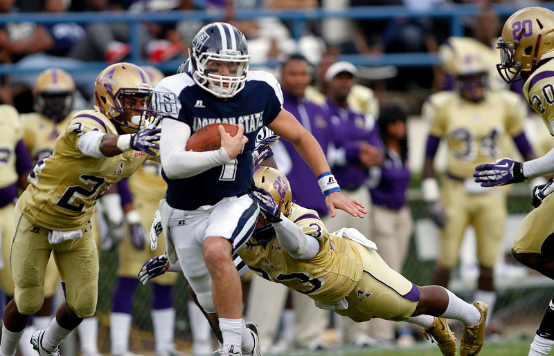Jackson State quarterback Clayton Moore runs past Alcorn defenders. (Charles A. Smith/For the Clarion Ledger)