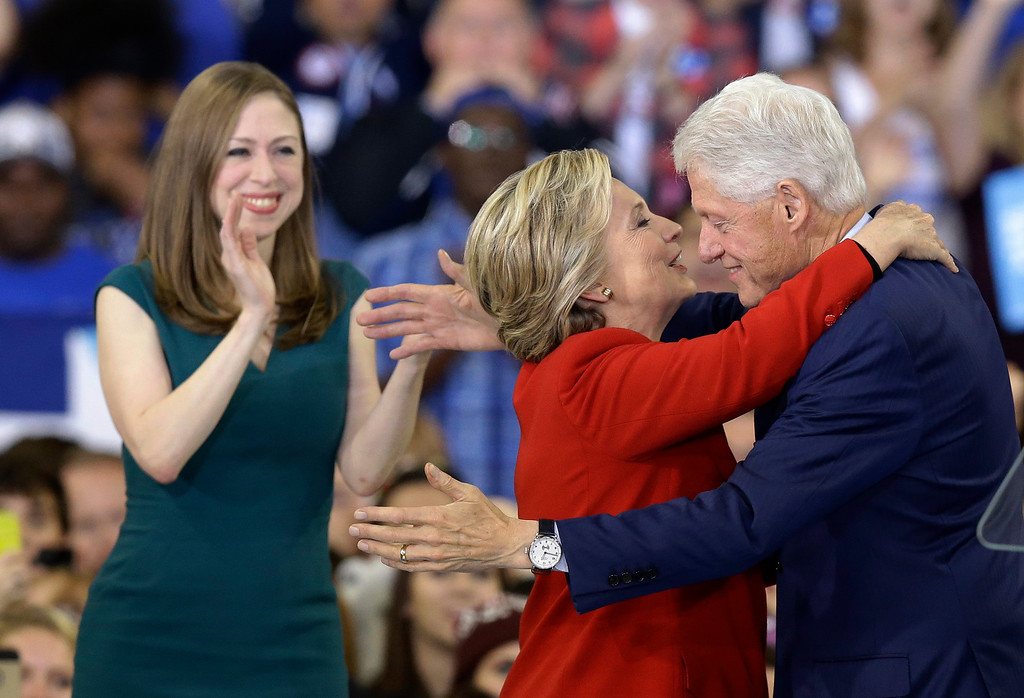 . Democratic presidential candidate Hillary Clinton hugs her husband, former President Bill Clinton as their daughter Chelsea Clinton looks on during a campaign rally in Raleigh, N.C., Tuesday, Nov. 8, 2016. (AP Photo/Gerry Broome)