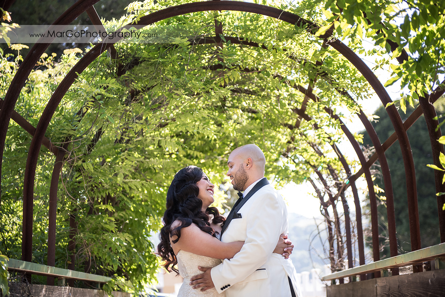 bride and groom hugging in green tunnel near Sunol's Casa Bella