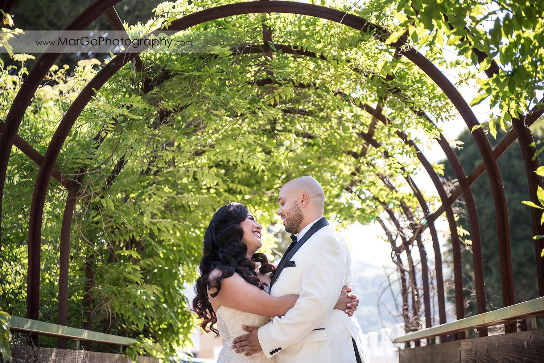 bride and groom hugging in green tunnel near Sunol's Casa Bella