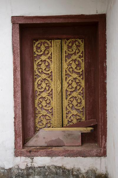 Elaborate art on temple window in Luang Prang, Laos