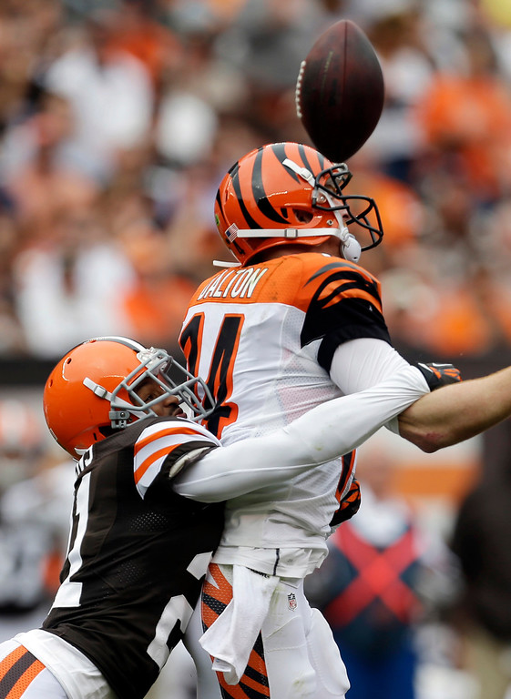 . Cleveland Browns defensive back Chris Owens, left, hits Cincinnati Bengals quarterback Andy Dalton, causing a fumble, in the third quarter of an NFL football game on Sunday, Sept. 29, 2013, in Cleveland. The Browns recovered. (AP Photo/Tony Dejak)