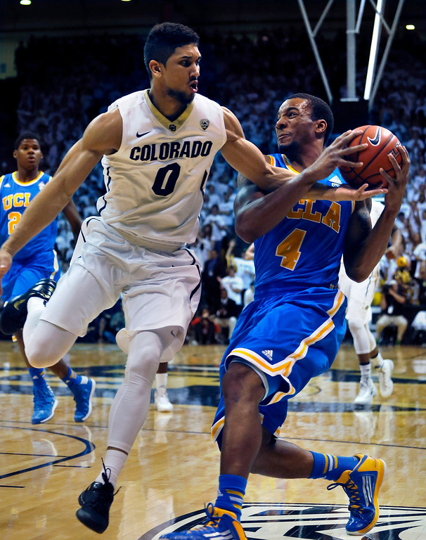 . UCLA\'s Norman Powell (4) tries to keep the ball from Colorado\'s Askia Booker during the first half of an NCAA college basketball game in Boulder, Colo., Thursday, Jan. 16, 2014. (AP Photo/Brennan Linsley)