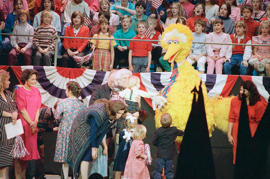 . First lady Barbara Bush stands behind children, Big Bird and actor Wilford Brimley as Marilyn Quayle, wife of the vice president, looks to her right, during  an Inaugural Celebration of the American Presidency for Young People in Washington, Jan. 21, 1989. (AP Photo/Dennis Cook)
