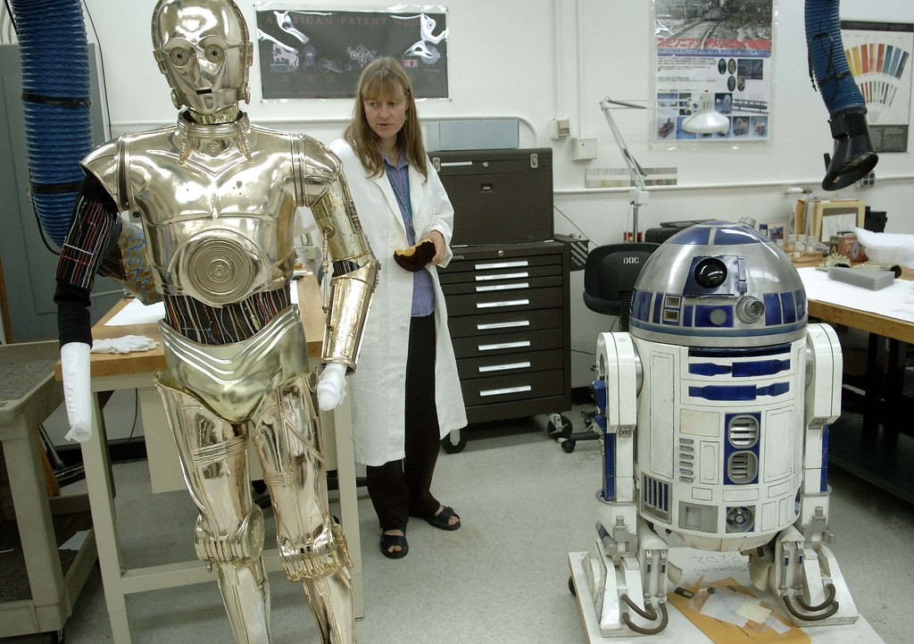 ". Beth Richwine, Objects Conservator at the Smithsonian\'s National Museum of American History, explains how they are preparing C3PO, left, and R2D2 from ""Star Wars,\"" to be moved for temporary exhibition while the museum is closed, Wednesday, Aug. 30, 2006, in Washington.  Dorothy\'s ruby slippers from \""The Wizard of Oz\"" will be part of the exhibit opening Nov. 17 at the nearby National Air and Space  Museum, along with R2D2 and C3PO from \""Star Wars,\"" President Lincoln\'s top hat, new artifacts from Hurricane Katrina and about 150 other items. (AP Photo/Kevin Wolf)"