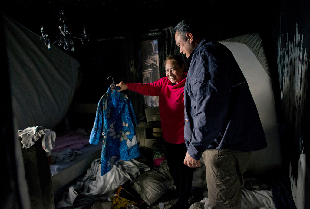 . In the background, Anna Paasi shows her husband Uatesoni Paasi a Hawaiian shirt she found in the bedroom of their house that was destroyed by a fire in December, in San Mateo, Calif. on Thursday, Jan. 2, 2014.  (LiPo Ching/Bay Area News Group)