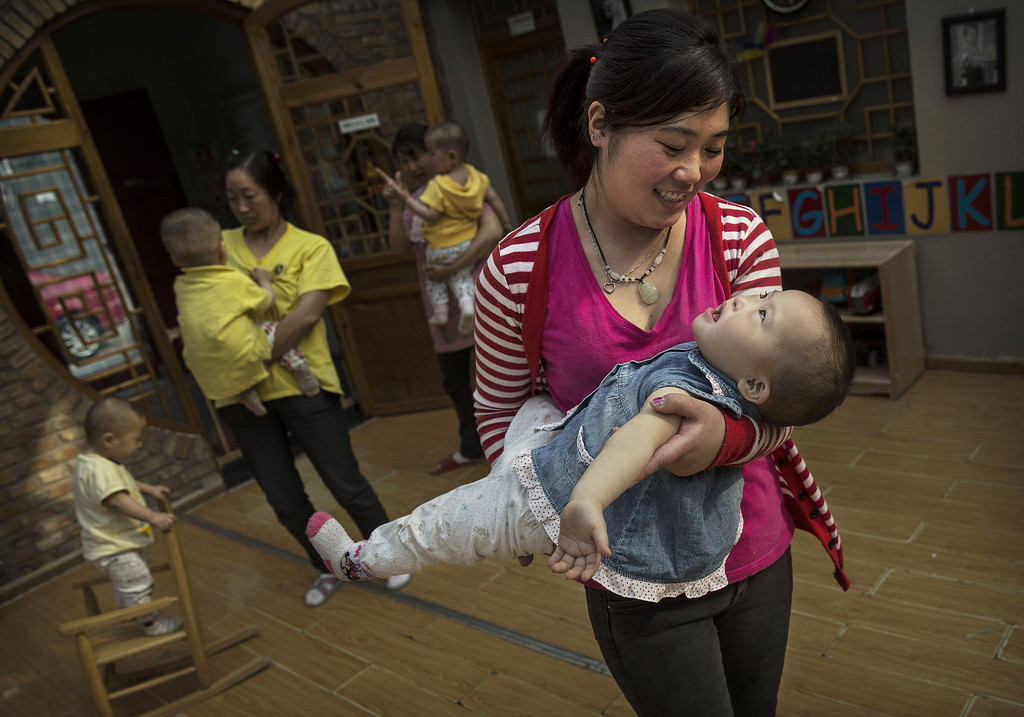 . A Chinese care worker carries a young orphaned girl at a foster care center on April 2, 2014 in Beijing, China.  (Photo by Kevin Frayer/Getty Images)