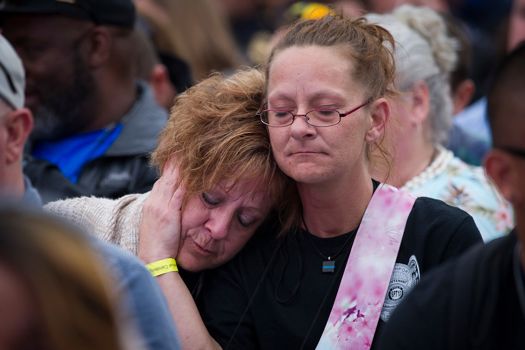 . Family members of police officers killed in the line of duty comfort each other during the National Law Enforcement Officers Memorial Fund 30th annual Candlelight Vigil, to commemorate new names added to the monument, on the Mall in Washington, Sunday, May 13, 2018. (AP Photo/Cliff Owen)