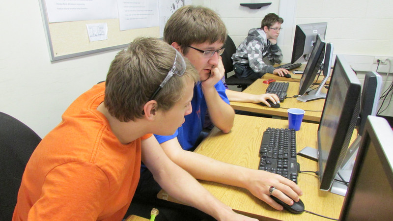 Adam works with Justin on a CAD prototype.