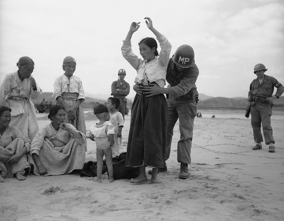 . U.S.military policeman searches Korean woman refugee for possible hidden weapons on Naktong River beach in South Korea on Sept. 27, 1950 after U.S. 24th Division drive across the river west of Taegu. Among onlookers in one youngster who obviously needs no search. (AP Photo/Gene Herrick)