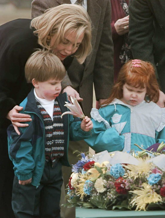 . US First Lady Hillary Clinton assists unidentified Oklahoma City bombing victims with a flower from a wreath 05 April in remembrance of the 168 victims of the 19 April 95 bombing at  the Alfred R. Murrah Federal Building in Oklahoma City, Oklahoma.  (PAUL J. RICHARDS/AFP/Getty Images)