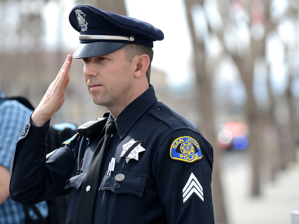 ". San Jose police Sgt. Brian Shab salutes as the Santa Cruz procession arrives at the HP Pavilion in San Jose, Calif. on Thursday, March 7, 2013. Thousands are expected at the pavilion to mourn the loss of the two SantaCruz police officers Loran ""Butch\"" Baker and Elizabeth Butler who lost their their lives in the line of duty on Feb. 26. (Dan Honda/Staff)"