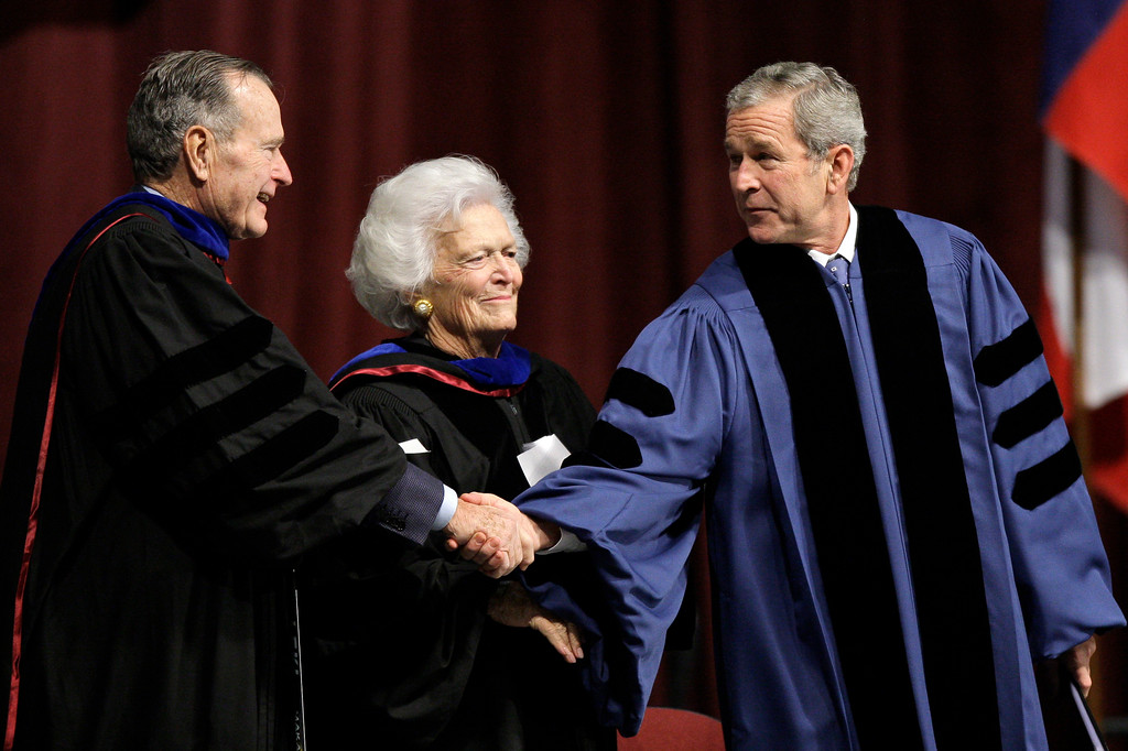. President George W. Bush, right, shakes hands with his father, former-President George H.W. Bush, left, as his mother, Barbara Bush stands at center during a commencement ceremony at Texas A&M University, Friday, Dec. 12, 2008, in College Station, Texas. (AP Photo/David J. Phillip)