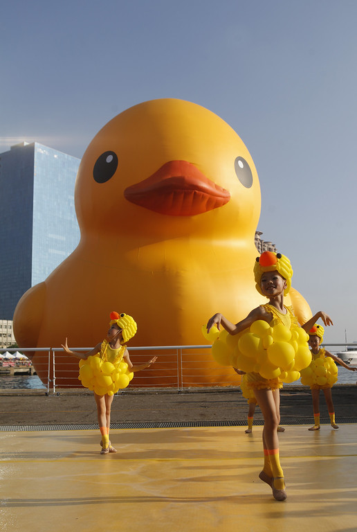 . Girls dress as ducks as people gather to see a giant Rubber Duck by Dutch conceptual artist Florentijin Hofman at Glory Pier on September 19, 2013 in Kaohsiung, Taiwan. (Photo by Ashley Pon/Getty Images)