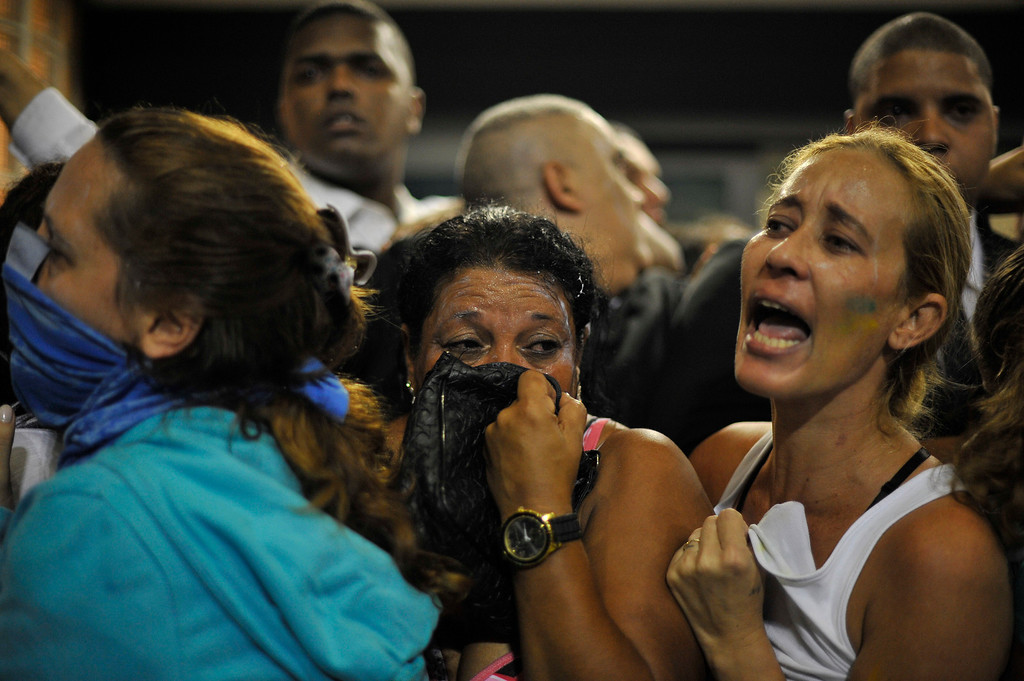 . Protestors take cover after police fired tear gas into the street in Rio de Janeiro, Brazil, June 20, 2013.   (AP Photo/Nicolas Tanner)