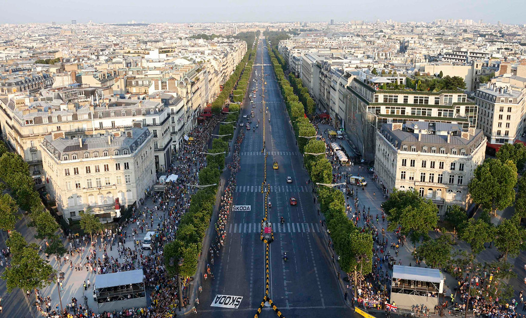 . The pack of riders cycles on the Champs Elysees avenue during the 133.5km final stage of the centenary Tour de France cycling race from Versailles to Paris Champs Elysees, July 21, 2013.  REUTERS/Jean-Paul Pelissier