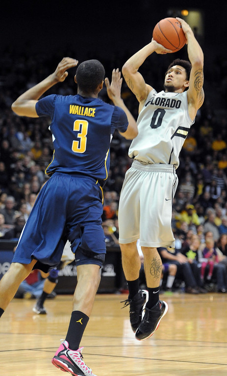 . Askia Booker of CU puts up a shot on Tyrone Wallace of Cal during the first half of the January 27th, 2013 game in Boulder. Cliff Grassmick/The Daily Camera