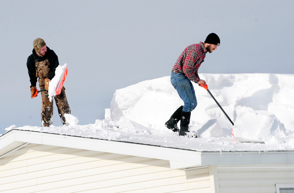 . D.J. Schloss, left, and Doug Metz, right, shovel off a roof on Abbey Lane in Alden, N.Y. Thursday, Nov. 20, 2014. The weight of the snow has caused problems around the area with roofs collapsing and buildings compromised. (AP Photo/Gary Wiepert)