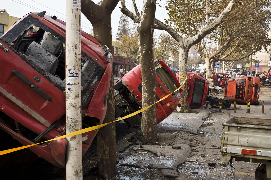 . Damaged vehicles lie by a street after an oil pipeline exploded, ripping roads apart, turning cars over and sending thick black smoke billowing over the city of Qingdao, east China\'s Shandong province on November 22, 2013, killing 35 people, authorities said, in the latest deadly industrial accident in the country.   AFP PHOTOSTR/AFP/Getty Images