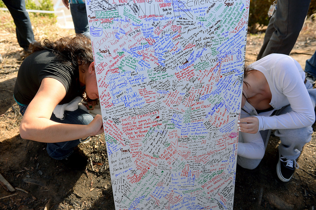 . People sign a memorial for Paul Walker and Roger Rodas, Sunday, December 1, 2013, at the scene of their fatal crash site in Valencia. (Photo by Michael Owen Baker/L.A. Daily News)