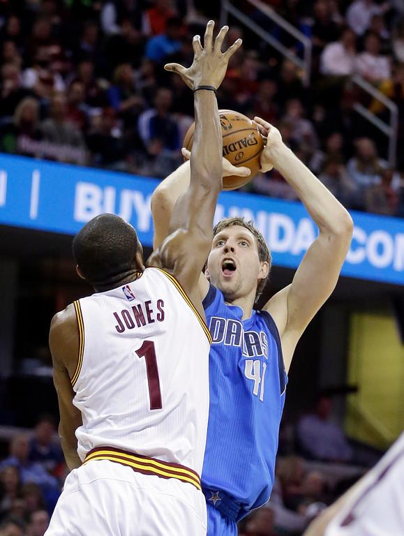. Dallas Mavericks� Dirk Nowitzki (41), from Germany, shoots over Cleveland Cavaliers\' James Jones (1) during an NBA basketball game Sunday, Jan. 4, 2015, in Cleveland. (AP Photo/Tony Dejak)