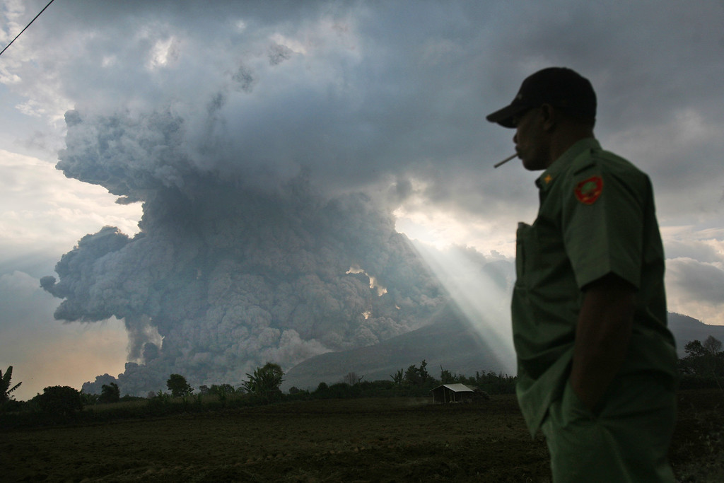 . An Indonesian man watches as Mount Sinabung erupts, in Tiga Kicat, North Sumatra, Indonesia, Monday, Oct. 13, 2014. Mount Sinabung, among about 130 active volcanoes in Indonesia, has sporadically erupted since 2010 after being dormant for 400 years. (AP Photo/Binsar Bakkara)