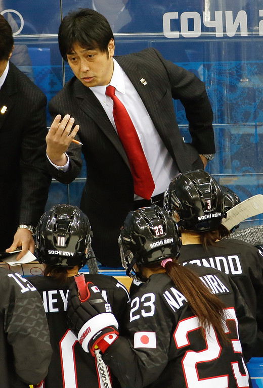 . Japan head coach Yuji Iizuka talks to the team in the bench during the third period of the game against Sweden during 2014 Winter Olympics women\'s ice hockey game at Shayba Arena, Sunday, Feb. 9, 2014, in Sochi, Russia. Sweden won 1-0. (AP Photo/Matt Slocum)
