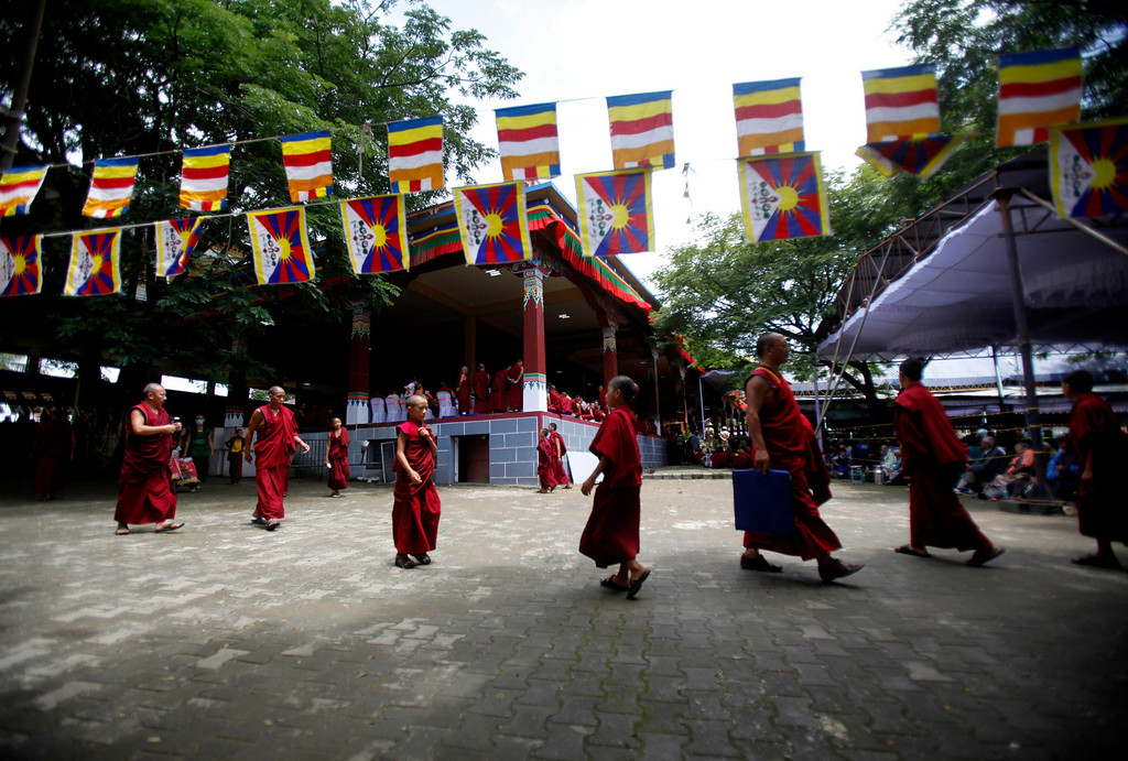 ". Tibetan monks walk around the Tibetan Buddhist monastery during an event organized to celebrate the 78th birthday of their spiritual leader the Dalai Lama in Bylakuppe, about 220 kilometers (137 miles) southwest of Bangalore , India, Saturday, July 6, 2013. Speaking after an interfaith meeting, he said 150,000 Tibetans living abroad represent ""6 million Tibetans (in China) who have no freedom or opportunity to express what they feel.\"" (AP Photo/Aijaz Rahi)"