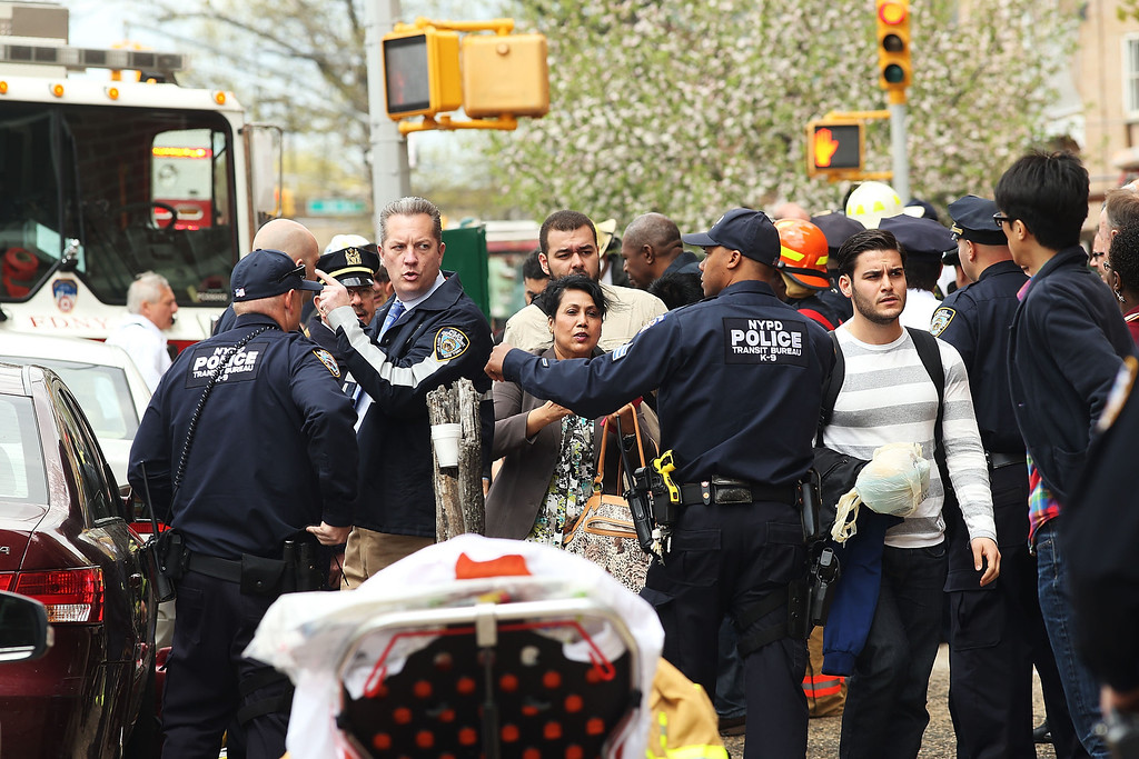. New York City firefighters, police and rescue workers use an emergency staircase to evacuate passengers from a derailed F train on May 2, 2014 in the Woodside neighborhood of the Queens borough of New York City. According to the Metropolitan Transportation Authority  (MTA) the express F train was bound for Manhattan and Brooklyn when it derailed at 10:40 a.m. about 1,200 feet from the 65th station in Woodside, Queens with hundreds of passengers on board.  (Photo by Spencer Platt/Getty Images)