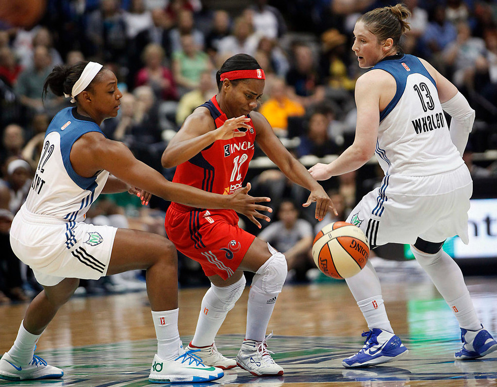 . Washington Mystics guard Ivory Latta (12) tries to grab the loose ball against Minnesota Lynx guards Monica Wright (22) and Lindsay Whalen (13) in the first half. (AP Photo/Stacy Bengs)