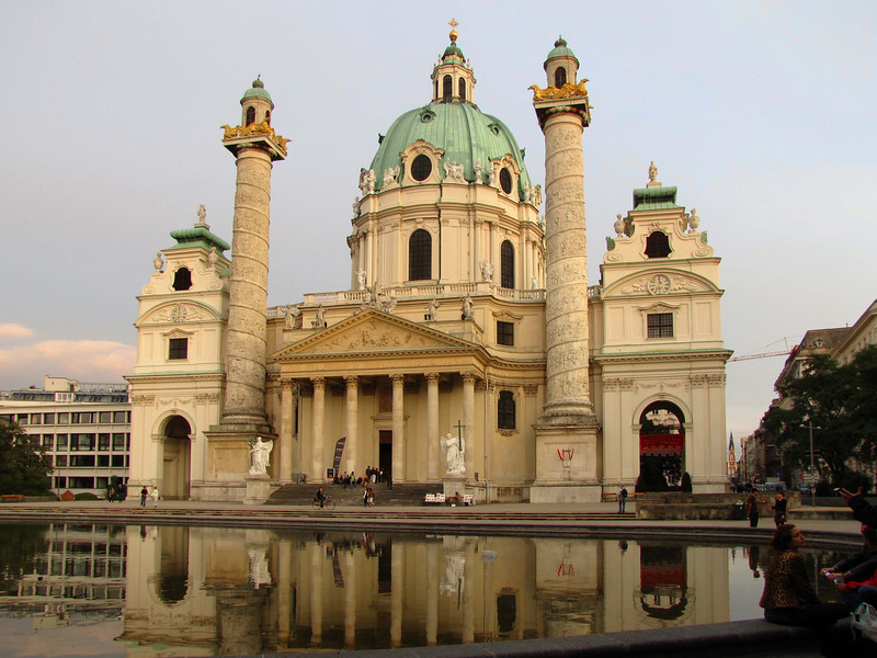 64-KarlsKirche. The central entry resembles a Greek temple. The pediment reliefs by Giovanni Stanetti show the Viennese suffering in the Plague of 1773