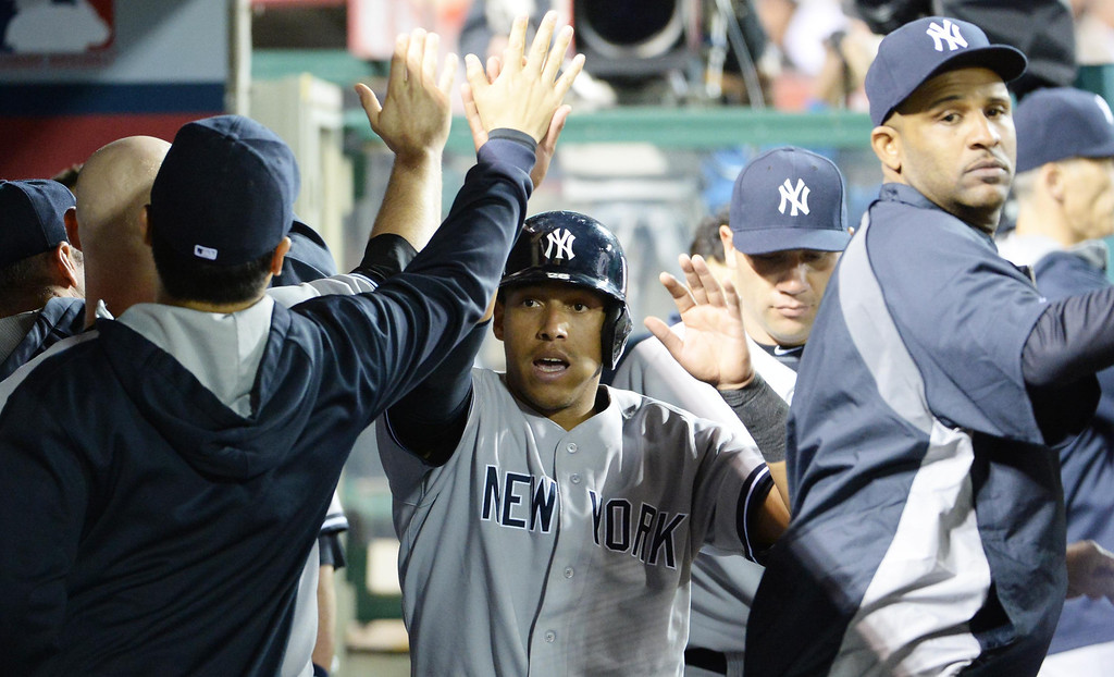 . New York Yankees\' Yangervis Solarte high fives teammates after scoring on a single by Alfonso Soriano (not pictured) in the eighth inning of a baseball game against the Los Angeles Angels at Anaheim Stadium in Anaheim, Calif., on Tuesday, May 6, 2014.  (Keith Birmingham Pasadena Star-News)
